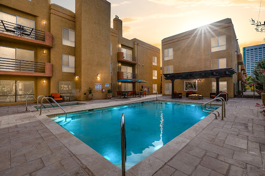 Toluca Terrace Apartments refreshing swimming pool with poolside firepit lounge area at dusk