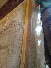 Photo: strip of hessian fixed to batten which doubles up as vertical plaster edge along door frame.  Hessian will contain bulk of fill-in straw render curved in to round off wall into door opening.