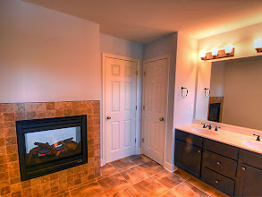 Photo: Double-side fireplace in the master bath of the HAMILTON