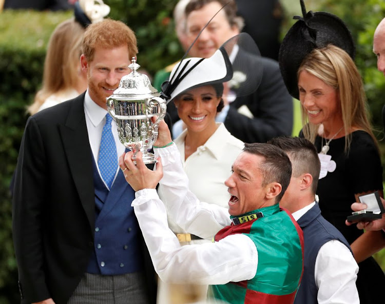 Frankie Dettori celebrates with a trophy after winning the St James's Palace Stakes as Britain's Prince Harry and Meghan, the Duchess of Sussex, look on. Picture: REUTERS