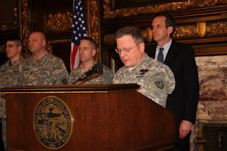 Photo:  Maj. Gen. Larry W. Shellito, State Adjutant General addresses family and friends at a deployment ceremony for 12 Soldiers from the Operational Mentoring Liaison Team in the Governor's Reception room at the State Capital in St. Paul, MN. Governor Pawlenty stands with Soldiers behind him.