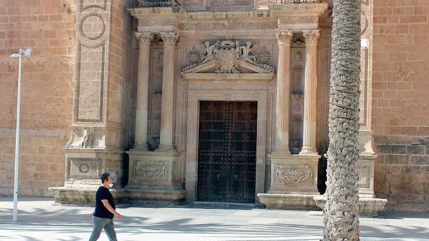 Un ciudadano  paseando por la Catedral con la mascarilla cubriéndole la barba mientras va fumándose un cigarro.