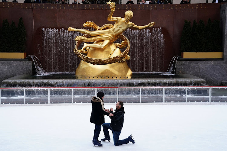 A man proposes marriage to his girlfriend, who said yes, at the Rockefeller Center in Manhattan.