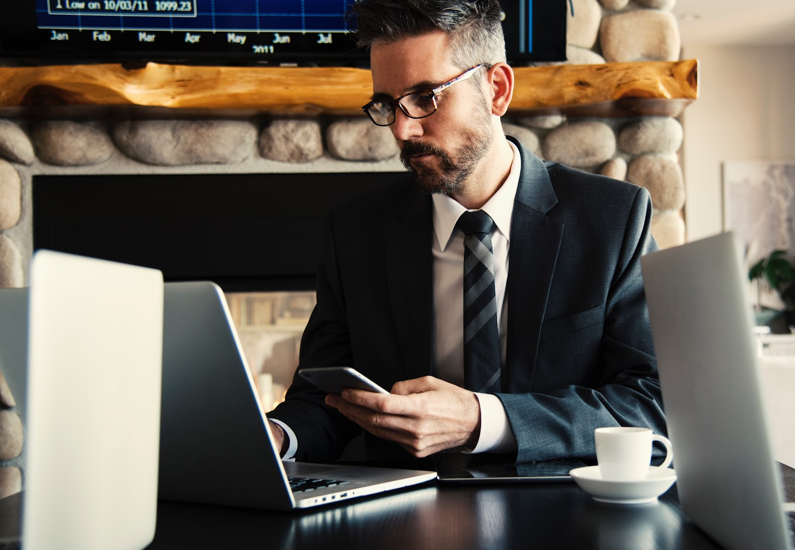 A man holds a phone and works on a laptop