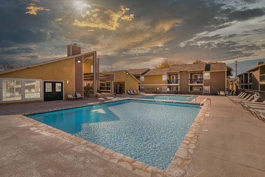 Copper Mill apartment swimming pool surrounded by pool furniture and apartment building at dusk