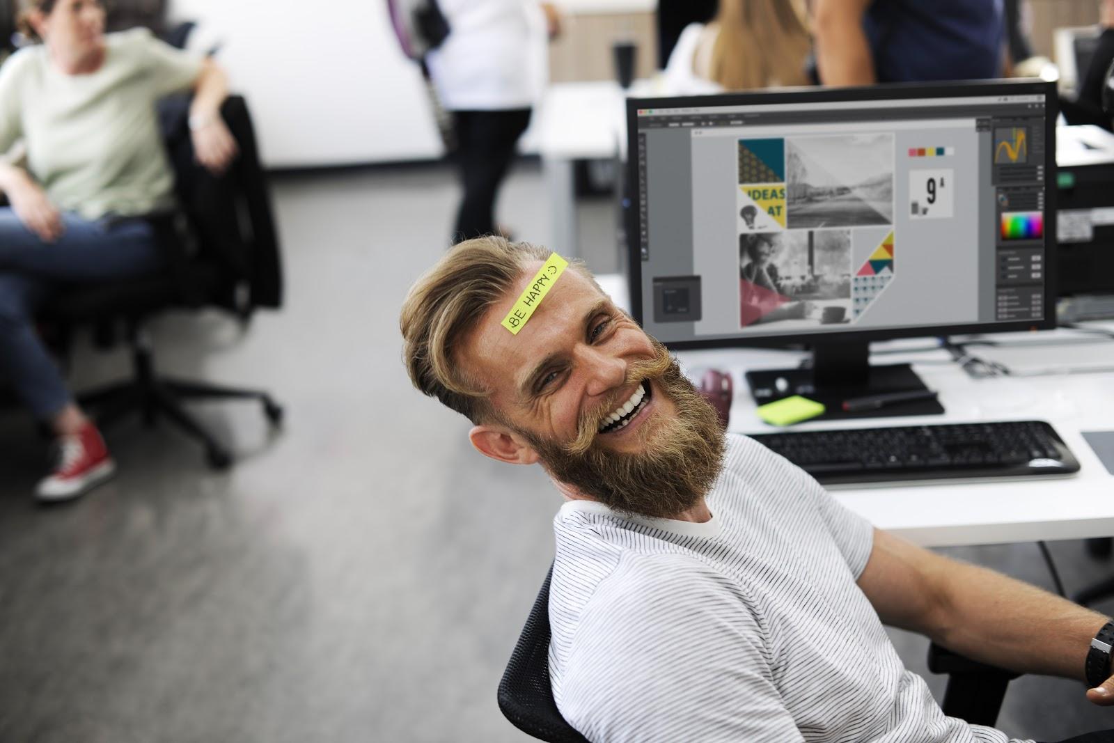 """Imagem de um homem jovem, feliz, com um post-it escrito """"be happy"""" em sua testa, sentado lateralmente de frente para um computador demonstrando que o investimento em o que é SQL aumenta a produtividade de seus colaboradores"""