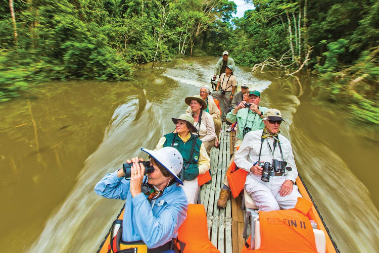 Travelers explore the Amazon River on a boat tour while on a Lindblad Expedition visit.