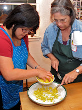 Photo: Sarah topping the noodles with diced pineapple while Peggy helps