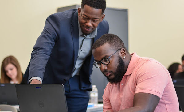 Man sitting at computer while another man stands and points at something on screen.