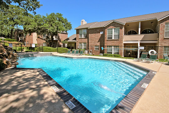 Swimming pool with lounge furniture next to apartment buildings