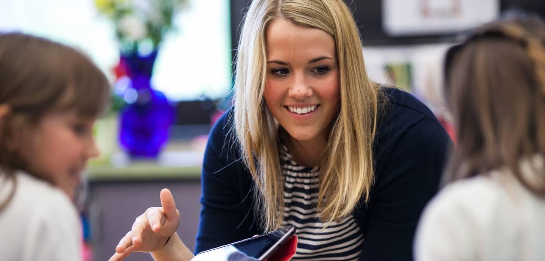 一位金髮的年輕女老師正在桌前和兩個年幼學生互動。