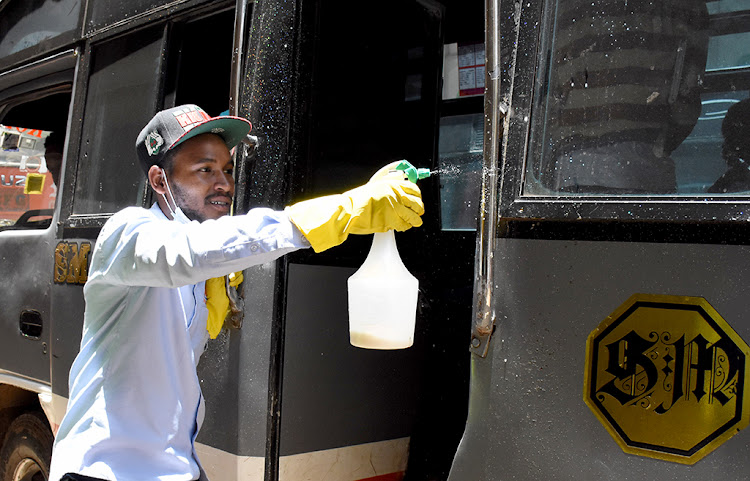 Job Odhiambo sanitizing PSV handles outside Avenida Lounge Restaurant along Moi Avenue on March 16.
