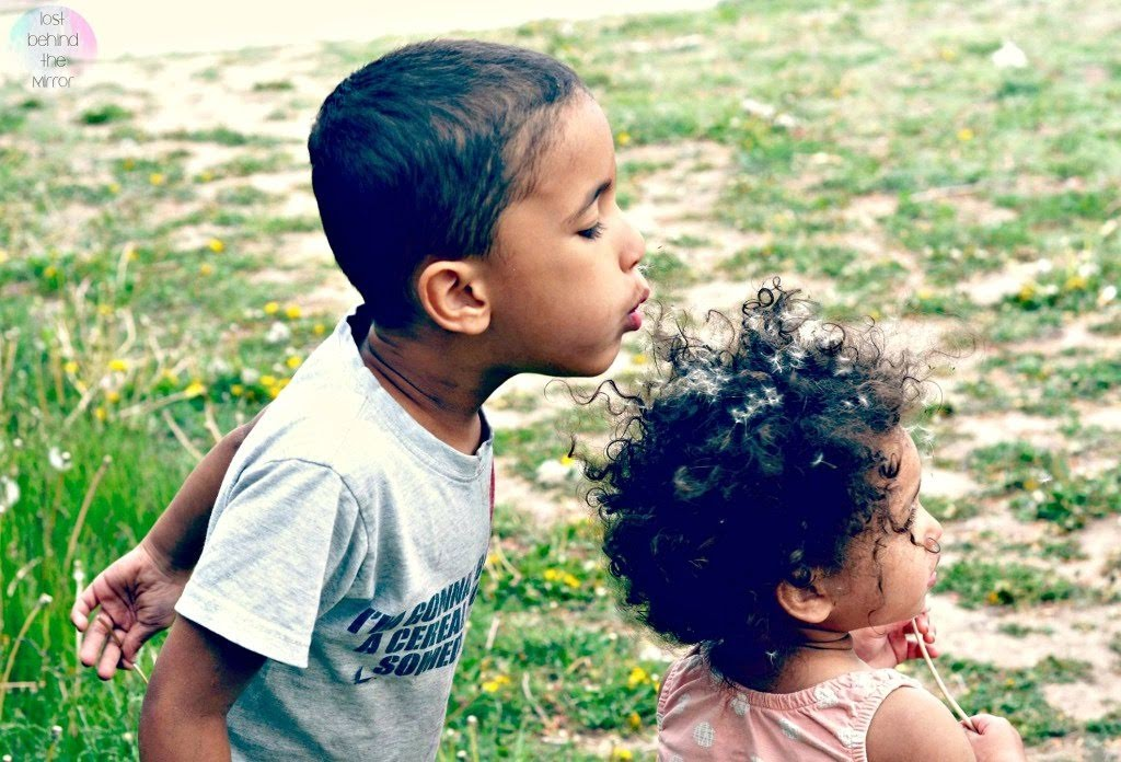 kids playing blowing dandelions