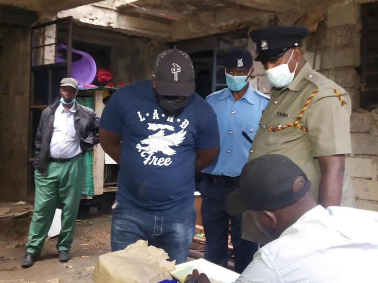 One of the suspects (in cap) being held by police officers at the scene in Ruiru on Monday, May 3, 2021