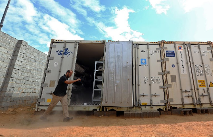 Ali Tuwaileb who is in charge of a high security anti-organised crime complex in Misratah where the bodies of Islamic State (IS) group fighters are being stored opens one of the refrigerated containers at a make-shift morgue on October 26, 2017. Around 700 bodies have been housed at the improvised morgue ever since IS jihadists were expelled in December 2016 from the coastal city of Sirte that had been their bastion in Libya.