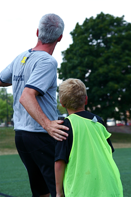 Soccer coach guiding a soccer player with hand on shoulder - Questions to ask a soccer coach