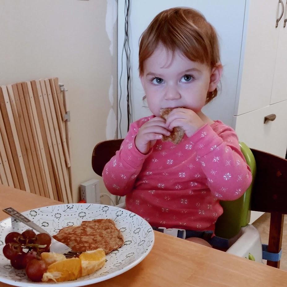 Toddler girl eating a pancake
