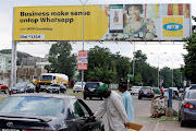 People stand near an advertising billboard for MTN  in Abuja, Nigeria.  Picture: REUTERS/AFOLABI SOTUNDE