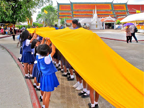 Photo: a teacher instructs school kids how to carry the sacred cloth above their heads