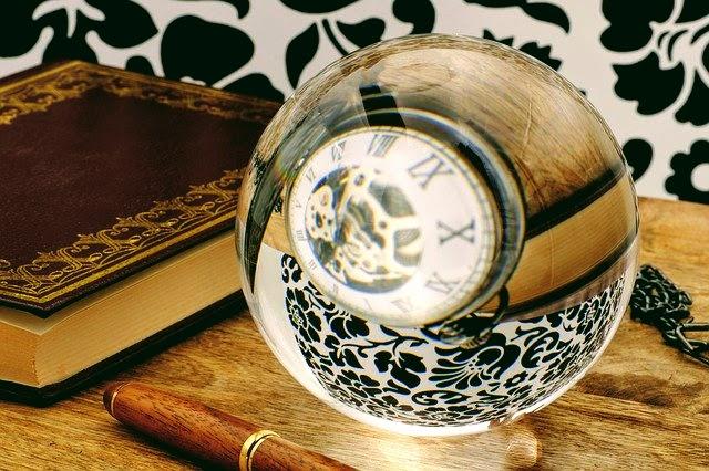 イメージ写真。ガラス玉に時計が写っている。傍にノートとペン