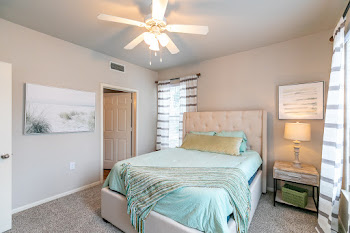 Model bedroom with light brown carpet, ceiling fan, and bed with light blue bedding