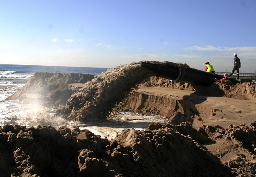 Sea water and sand gush from a sand-pumping pipeline in Durban. While local residents have welcomed the belated operation to replenish sand in the North Beach area, many Local divers and fishermen fear that continued smothering of Vetch's Pier near the harbour mouth is destroying unique marine recreation assets. Picture: TONY CARNIE