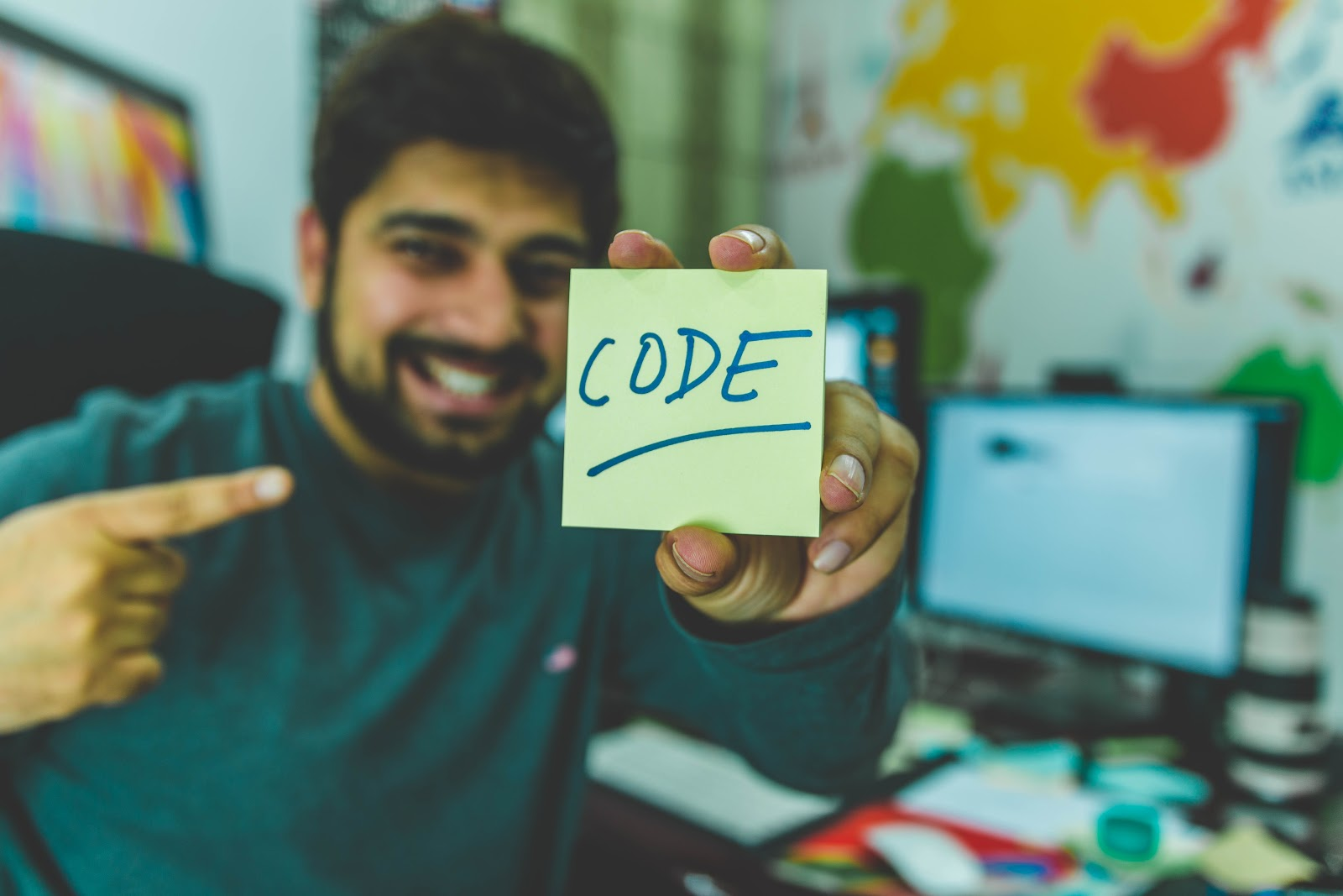 a man displaying the word 'code' on a sticky note