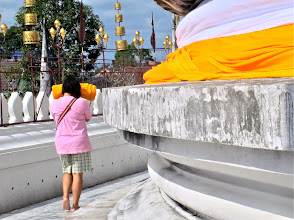 Photo: a worshipper with a roll of sacred cloth circumambulates the chedi in prayer