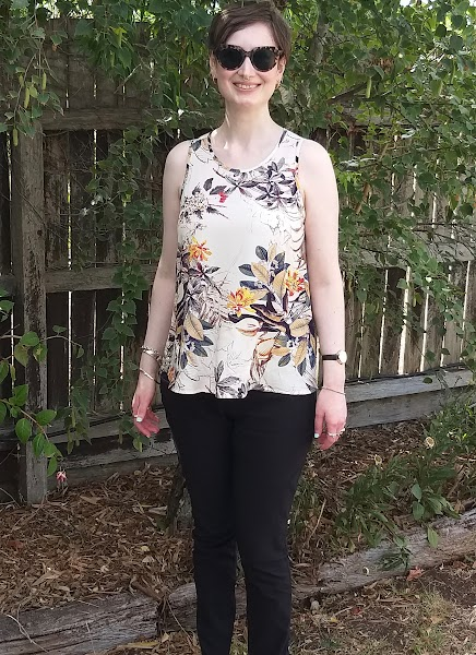 Siobhan stands in front of a garden fence. She wears a tank top with narrowed shoulders and slight scoop neck, in a beige printed rayon with slim-fit black pants. She wears large tortoiseshell sunglasses and is smiling.
