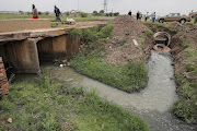 Raw sewage (right) merges with a clean water source near Sharpeville, south of Johannesburg.