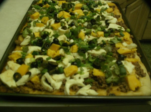 Placed onions and cilantro on the pizza and cheese!