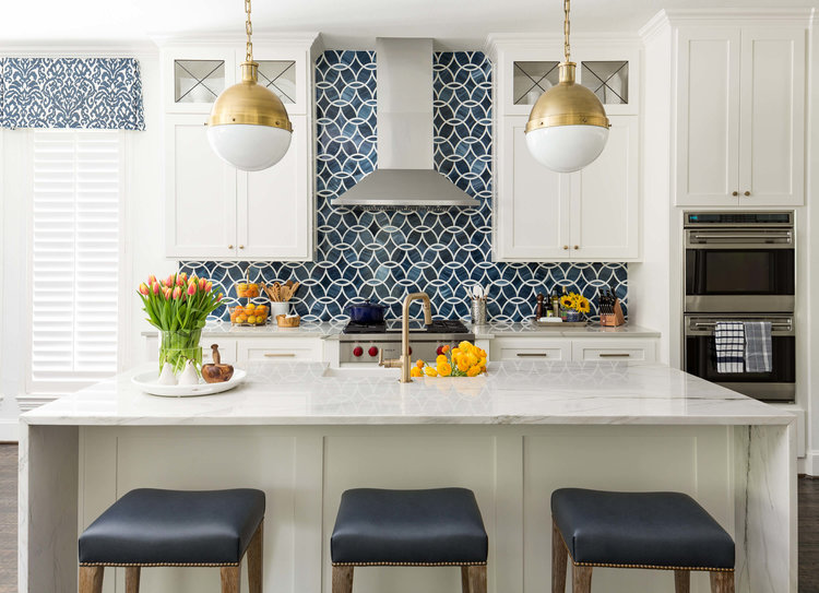 bright white shaker cabinets with navy glass backsplash tile, center waterfall island with white marble, navy barstool seating and brass globe pendant lights