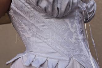 Photo: Corset Midbust Ref.: CRM 1790 01 Valor: R$ 480,00 Corset Midbust (Stays), até a cintura em brocado branco, sarja e algodão, com detalhe em cetim. Confeccionado com barbatanas flats. Confeccionado em brocado na camada externa, duas camadas de sarja 100% algodão e uma camada de entretela. São 4 barbatanas flats em aço temperado revestido ou aço inóx mais busk de madeira frontal para dar sustentação. O valor padrão refere-se às medidas até 89 cm de cintura. Para peças com medidas maiores, entre em contato.  Verifique disponibilidade de modelo, tecidos e cores entrando em contato. O tom pode variar dependendo da calibragem de cor do seu monitor ou celular.  Também disponível nos tecidos e cores: - Brocado bege; - Brocado branco; - Brocado rosa.