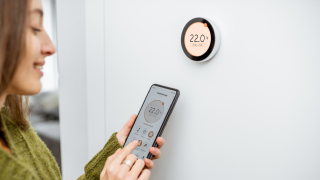 woman setting thermostat from smartphone
