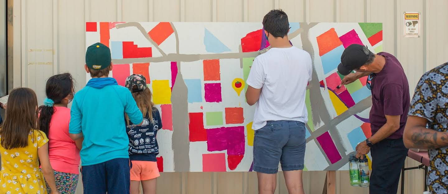 Adults and children painting an interactive mural of a map of San Jose.