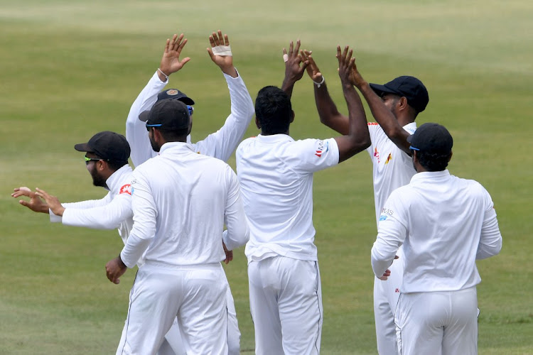 Sri Lanka's fast bowler Vishwa Fernando celebrates with teammates after taking a wicket of Hashim Amla on the first day of the 1st Test match at Durban's Kingsmead on February 13 2019.