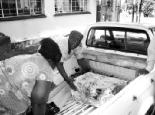 BEREAVED: Flora Manyike is helped by a relative to settle hergrandson's coffin in a bakkie at Tintswalo Hospital. 19/03/09. Pic. Riot Hlatshwayo. © Sowetan.