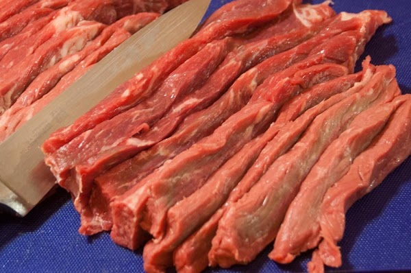 Using a nice sharp knife cut the beef into 1/8-inch (.3cm) slices.