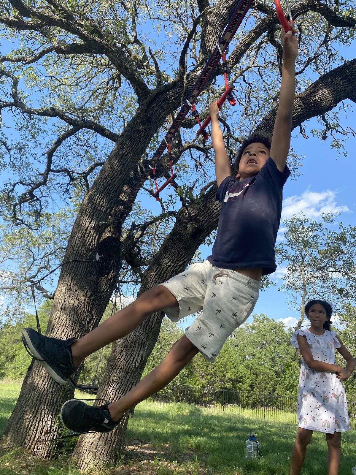 boy swinging across a backyard ninjaline