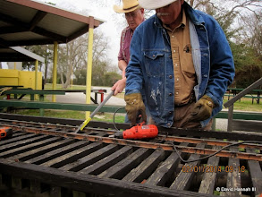 Photo: Rick White using a corded drill with Art Morris prying up the rail.   2014-0201  DH3