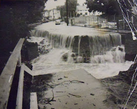 Photo: Water pours over the edge of a washed-away street.
