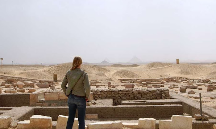 Woman gazes into the pyramids of giza from the saqqara pyramids