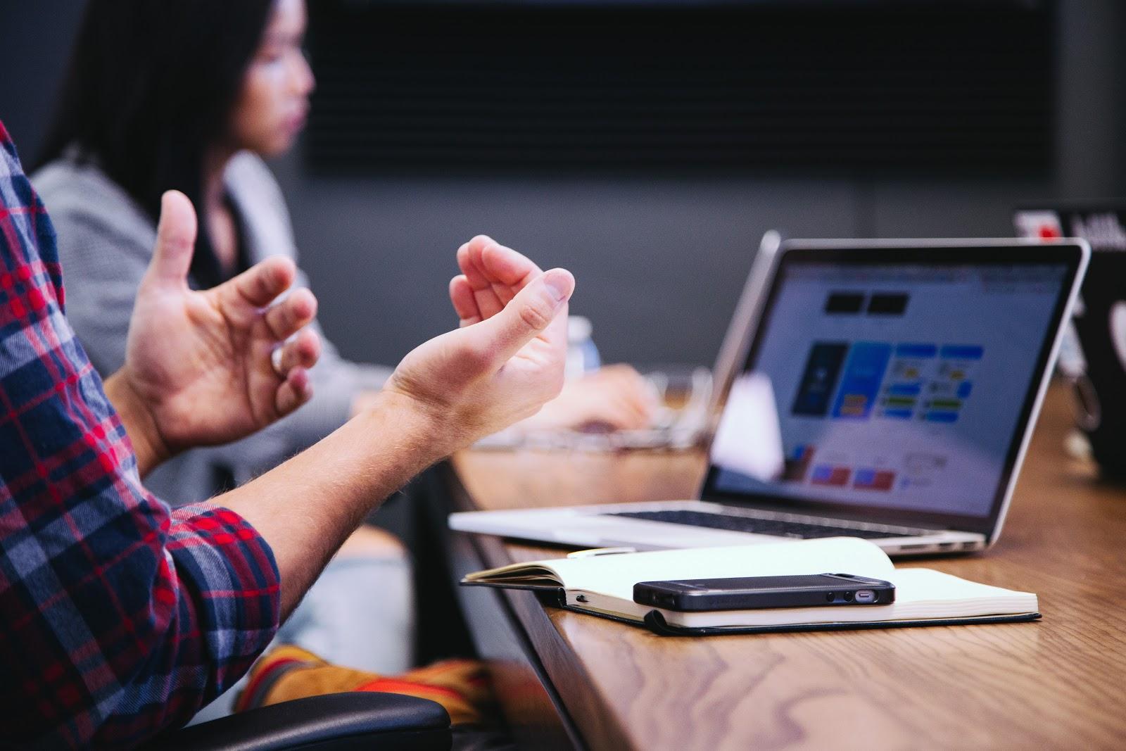 Uma mão fazendo gestos de explicação em uma mesa.