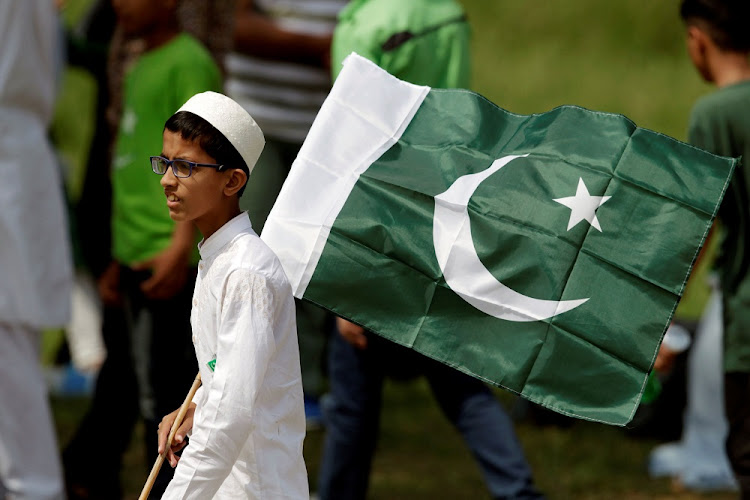 A young man holds a national flag in Islamabad, Pakistan. Picture: REUTERS