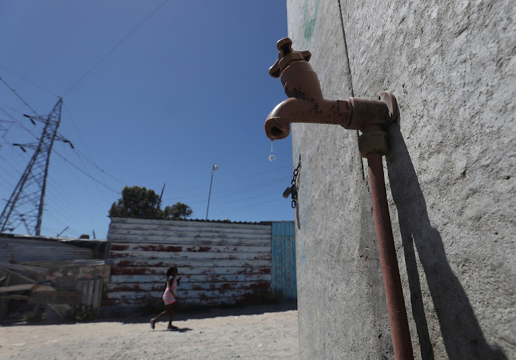 Residents walk past a leaking communal tap in Khayelitsha township, near Cape Town. File photo.