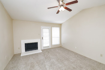 Living room with carpet, light walls, ceiling fan, and fireplace