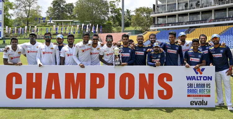 The Sri Lanka cricket squad players celebrate with the trophy after winning their two-match test series against Bangladesh 1-0.