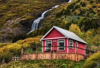 "Photo: Little Elves, Little Waterfall  Going into one of the valleys by Isafjordur takes you to many little homes near waterfalls.  I thought this one was quite lovely.  And if you look to the left there, you'll see the tiny homes they also built for the elves.  I was editing this photo at dinner one evening in Isafjordur.  One of the waitresses saw this house, recognized it, and said, ""Oh that's jklasdj(jkasdj^dhsaj"".  Of course, I am doing my best to approximate the Icelandic language there...  Read more at the Stuck in Customs blog here:  http://www.stuckincustoms.com/2011/08/30/little-elves-little-waterfall/"