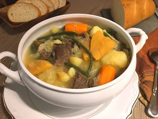 Stew In A Tureen With Slices Of Bread In The Background.