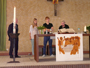 Photo: Mevr. Kints reikt namens de wijkgemeente Engelse bijbeltjes uit